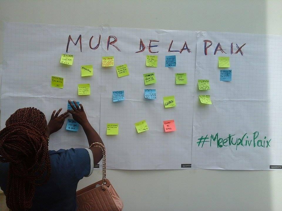Une participante affichant son mot sur le Mur de la Paix, crédit photo : Magloire Zoro