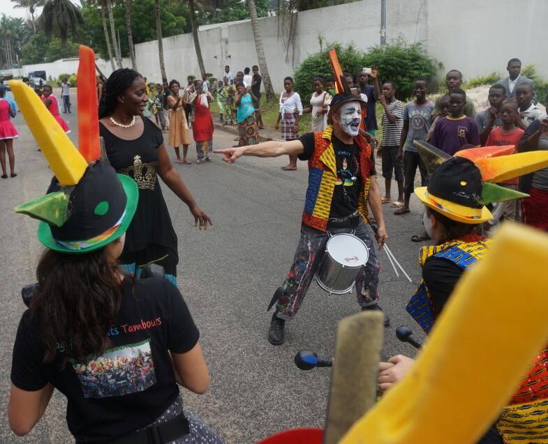 La Directrice du FIPRE, Mme Kiya Dongossi et Mouhss des Magiques Petits Tambours entourés par des curieux lors de la parade. Crédit photo : Magloire Zoro